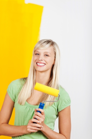 Smiling beautiful woman painting interior wall of home photo
