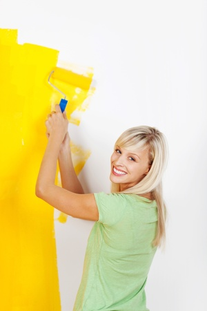 Happy smiling woman painting interior white wall in yellow color of new house photo