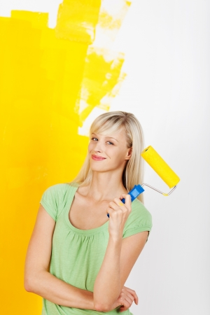 Happy smiling female painting interior white wall in yellow color of new house Stock Photo - 20662733