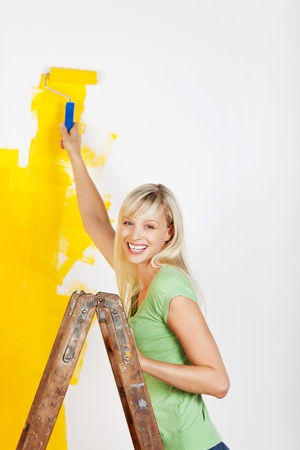 Smiling woman painting interior white wall in yellow color of new house Stock Photo - 20662734