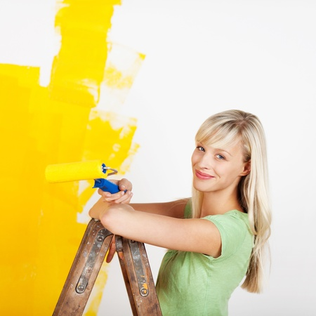 Smiling female painting interior white wall in yellow color of new house Stock Photo - 20651462