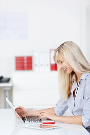 Smiling woman sitting on chair while browsing through her laptop photo