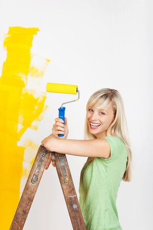 Happy woman painting interior white wall in yellow color of new house Stock Photo - 20662336