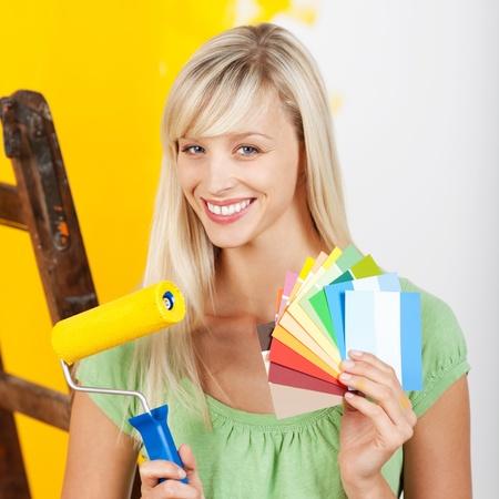 pintor de casas: Mujer sonriente que sostiene un cepillo del rodillo de pintura y carta de colores de pintura Foto de archivo
