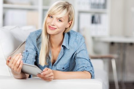 unwinding: Beautiful woman smiling and holding her tablet over the blurred background