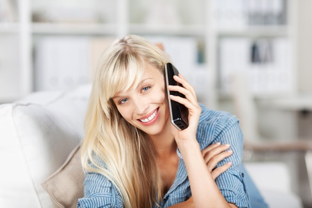 landline phone: happy blond female calling using her cellular phone