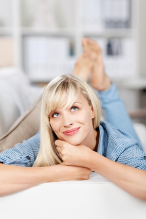 young girl barefoot: Lying female on couch having daydreaming over the blurred background