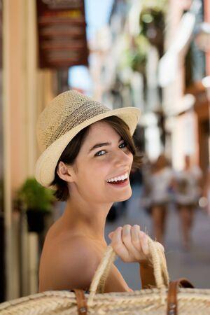 chapeau de paille: Rire femme faire du shopping avec un centre de paille dos en bandoulière sur son épaule et un chapeau de paille à la mode dans un environnement urbain