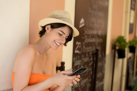 Attractive short haired young woman smiling while writing a message on her mobile phone photo
