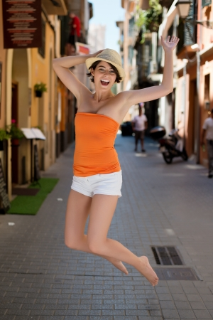 exuberant: Exuberant high-spirited young woman jumping for joy in a narrow urban street in a summer sunhat , shorts and bare feet while traveling on vacation Stock Photo