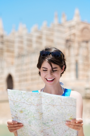 Beautiful young woman standing in the sunshine reading a handheld tourist map while on holiday in Mallorca photo