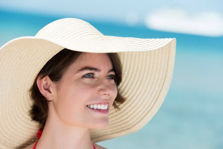 brim: Closeup portrait of the face a beautiful brunette woman in a wide brimmed floppy straw sunhat posing at the sea Stock Photo