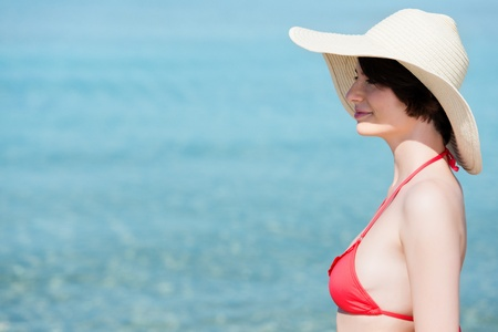 Beautiful woman in a red bikini and wide brimmed straw sunhat posing sideways at the seaside against a blue ocean with copyspace photo