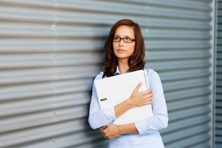Pensive businesswoman holding a large white binder clutched to her chest leaning against a corrugated metal wall photo