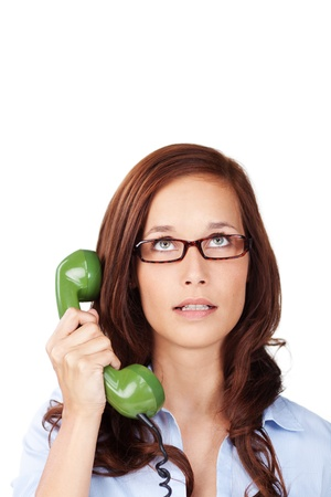 discontented: Exasperated woman lifting a green telephone receiver from her ear and raising her eyes to heaven for inspiration isolated on white