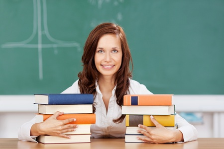 Smiling attractive young female student with her textbooks sitting at a desk in the classroom in front of the blackboard photo
