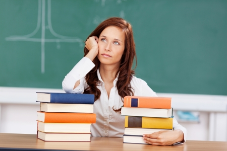 demotivated: Demotivated student looking for inspiration sitting behind two piles of textbooks resting her head on her hand and staring off into space lost in thought Stock Photo