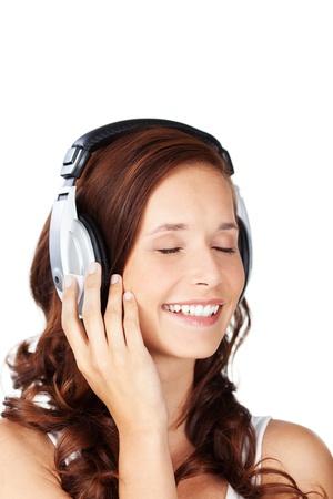 letras musicales: Mujer joven que escucha la música que lleva un par de auriculares con los ojos cerrados en el disfrute mientras se escucha la banda sonora