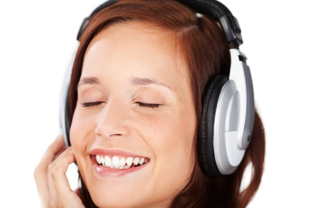 blissful: Blissful happy woman listening to music through earphones with her eyes closed and a beautiful smile