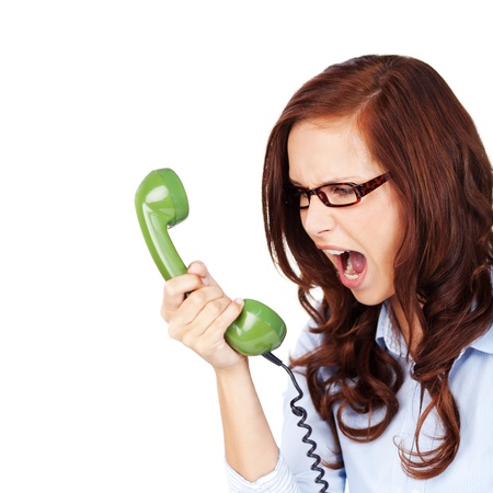 verbal communication: Young woman wearing glasses yelling at a green telephone handset that she is holding in her hand, isolated on white