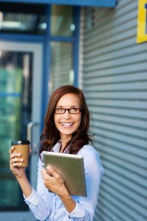 vivacious: Vivacious young business woman wearing glasses enjoying a coffee break outside the office building holding a cup of coffee in one hand and her tablet-pc in the other