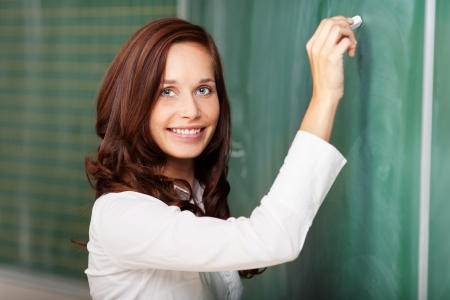 Smiling attractive young female teacher standing with her hand raised writing on a blank blackboard