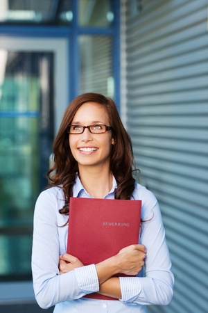 clutches: Happy woman clutching a red folder or binder and wearing glasses watching something in the air with a big smile