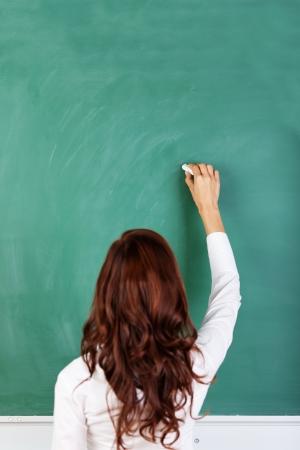 educadores: Vista trasera de un estudiante o profesor con la escritura morena de pelo largo en una pizarra verde en blanco o pizarra con copyspace Foto de archivo