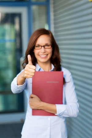 clutching: Enthusiastic young woman clutching a red folder giving a thumbs up of approval and success with focus to her hand