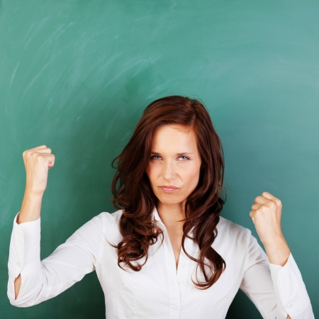 Angry attractive young woman standing against a blank blackboard shaking her fists in the air