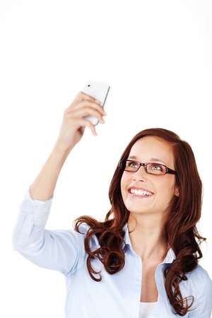 Attractive young woman wearing glasses smiling in delight as she reads an SMS on her mobile phone isolated on white photo