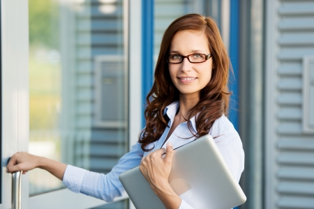 Attractive young woman wearing glasses carrying a laptop and opening the exterior door to a commercial building photo