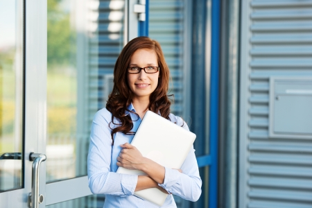 Businesswoman leaning on the door and holding a laptop photo