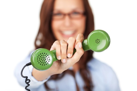 retro telephone: Smiling young woman holding out a green telephone handset in her extended hand offering it to the viewer with shallow dof Stock Photo