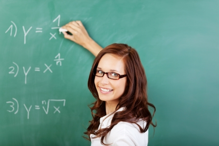 Friendly smiling female teacher or student standing in front of a green blackboard in the classroom writing mathematical equations photo