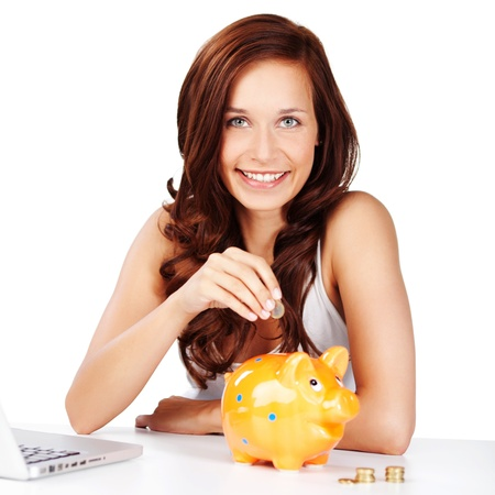 Young woman sitting at a table saving her change placing coins in a piggy bank as she saves for retirement or to pay for a dream to come true photo