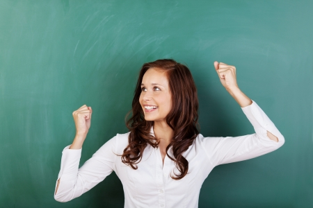 passed: Successful student rejoicing at passing her grades standing in front of a blank green chalkboard raising her fists in the air in jubilation