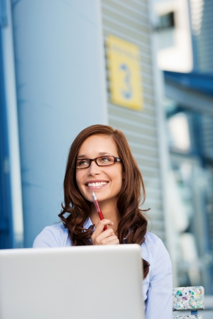 Smiling businesswoman holding a pen against the blurred background photo