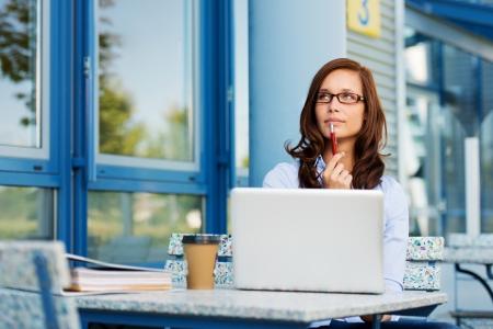 예쁜 여자가 펜으로 조롱하고 그녀의 노트북과 커피 숍에 앉아있는 동안 피사체를 통해 생각의 사진.
