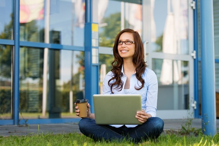 crosslegged: Image of a young woman smiling on something, while holding coffee and laptop, sitting crosslegged in the lawn.