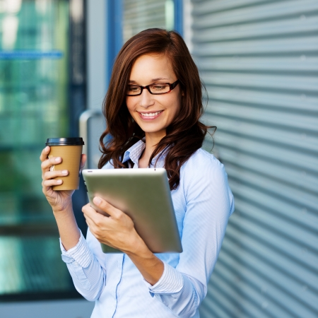 Attractive young woman wearing glasses drinking coffee and reading her tablet-pc while standing outside a commercial building