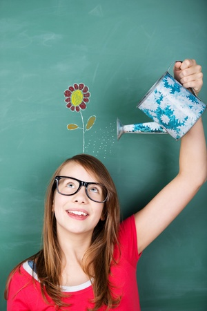 watering can: Conceptual image of an intelligent young schoolgirl wearing glasses making new ideas grow, by watering a flower drawing in a green chalkboard, with a gardening watering can