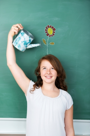 watering: Conceptual image of a pretty young schoolgirl making new ideas flourish, by watering a flower drawing in a green chalkboard, with a gardening watering can