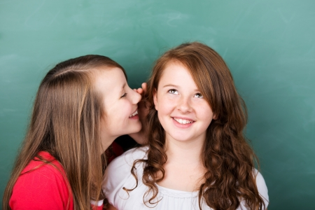 Portrait of female student telling a secret to her friend in a close up portrait Stock Photo