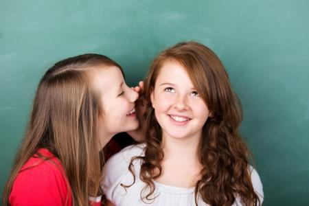 niños platicando: Retrato de alumna dice un secreto a su amiga en un primer plano retrato