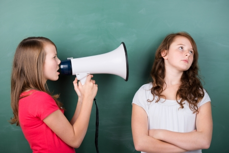 heard: Conceptual image of a schoolgirl trying to make herself heard by using a megaphone close to another girls ears, who ignores her Stock Photo