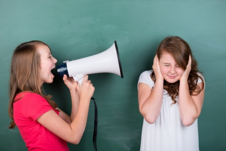 Conceptual image of a schoolgirl making herself loudly heard by using a megaphone close to another girl, who tries to ignore her by covering her ears, or in pain photo