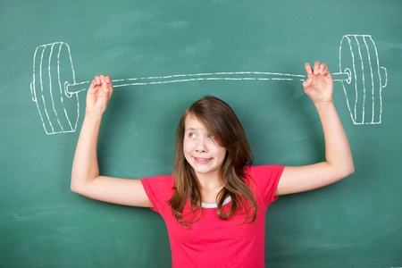 clenching: Conceptual image of a young schoolgirl trying to overcome a hard task by lifting a heavy barbell drawn in chalk in the green chalkboard Stock Photo
