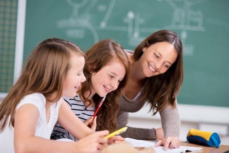 Elementary students listening to female teacher in school classroom