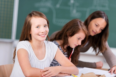 proud: Smiling student with her classmate listening to teacher in school classroom
